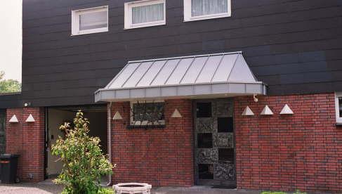Vordach integriert in bestehende Fassade, Material: Zink, vorbewittert, Deckung: Stehfalz